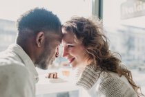 Cheerful couple in sweaters bonding by window — Stock Photo