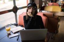 Mujer elegante en laptop con barbilla en mano y mirando a cámara - foto de stock