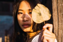 Retrato de mulher jovem inclinada segurando folha seca e olhando para a câmera — Fotografia de Stock