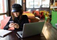 Стильная девушка сидит за ноутбуком и просматривает смартфон — стоковое фото