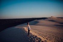 Веселая женщина, стоящая на песчаной дюне и наслаждающаяся солнцем . — стоковое фото