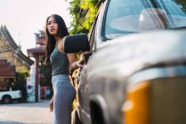 Young woman leaning on car and looking away — Stock Photo