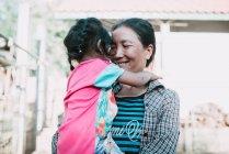 Nong Khiaw, Лаос: Посміхаючись жінка обіймати дівчинка на вулицю села. — стокове фото