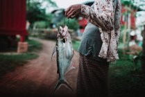 Midsection of woman holding big fish while walking on village street. — Stock Photo