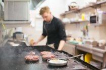 Cuoco irriconoscibile in piedi su cucina di ristorante mentre polpette e uova friggono su stufa — Foto stock