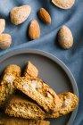 Вид зверху cantuccini печиво на тарілку і мигдалю — стокове фото