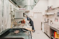 Side view of chef working on kitchen in restaurant. — Stock Photo