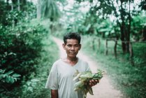 LAOS, 4000 ISLANDS AREA: Senior holding pile of leaves and looking at camera at country path. — Stock Photo