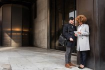 Stylish adult man and woman standing at street and browsing tablet on the street. — Stock Photo