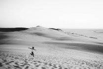 Fernblick über Frau fröhlich läuft auf Sanddünen — Stockfoto