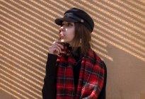 Élégante jeune femme se penchant au mur et à la recherche de côté — Photo de stock