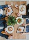 Desde arriba la vista de la pareja sentada en el restaurante a la mesa con grandes hamburguesas apetitosas. - foto de stock