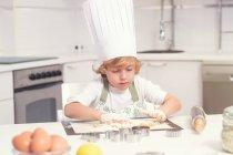 Ragazzino allegro sveglio rotolamento impastare sulla cucina a casa — Foto stock