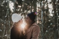 Sensual couple bonding in winter forest over sunset beams — Stock Photo