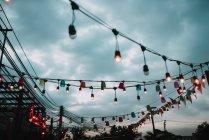 Belle luci appese su pali sopra il cielo nuvoloso — Foto stock