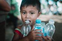 LAOS, 4000 ILHAS ÁREA: Menino com garrafas de plástico olhando para a câmera — Fotografia de Stock