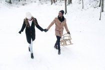 Happy romantic couple with sledge walking at forest — Stock Photo
