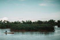Vue lointaine de l'homme assis sur un bateau et le conduisant sur une large rivière près d'une petite île . — Photo de stock