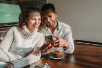 Bonding couple using smartphone in cafe — Stock Photo