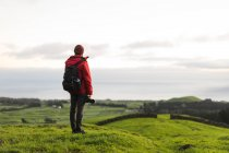 Rear view of tourist with camera on field with rolling hills — Stock Photo