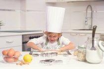 Милый веселый мальчик прокатки Замесить на кухне счетчик — стоковое фото