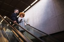 Stylish man and woman with smartphone riding down on moving stairs. — Stock Photo