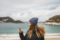 Young woman in hat using smartphone at ocean — Stock Photo