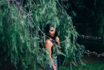 Pretty woman posing in fir branches — Stock Photo