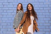 Mulheres jovens alegres em pé e abraçando a parede azul. — Fotografia de Stock