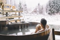 Couple embrassant et relaxant dans un bain profond en hiver — Photo de stock