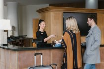 Reception worker giving key to family at hotel — Stock Photo