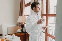 Homem de roupão de banho de pé com copo e olhando para a janela — Fotografia de Stock