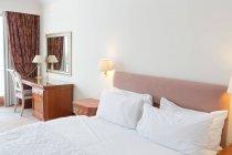 Interno della camera d'albergo con letto bianco e tavolo in legno — Foto stock