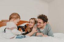 Familia joven alegre con el niño en la cama - foto de stock