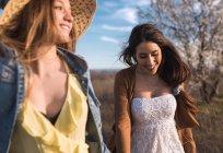 Fröhliche Frauen Hand in Hand und Wandern auf Feld im sonnigen Tag — Stockfoto