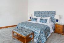 Interno della camera di albergo con letto bianco e blu — Foto stock