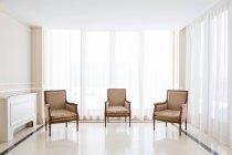 Три кресла, помещены в большой свет гостиничном номере — стоковое фото