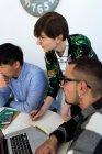Grupo de colegas alegres con gadgets en reunión - foto de stock