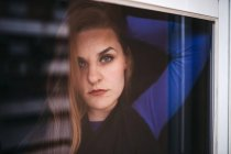 Задумчивая женщина, прислонившись к окну и посмотрев в камеру — стоковое фото
