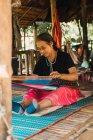 ЧАНГ-РАЙ, Таиланд - 12 февраля 2018 года: Старшая азиатка, сидящая дома и обрабатывающая шерсть . — стоковое фото