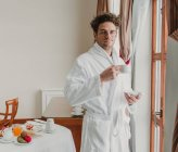 Young man in bathrobe posing with cup at hotel room — Stock Photo