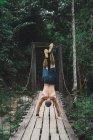 Rückansicht des nackter Oberkörper Mann auf Händen auf trashigen Holzbrücke im grünen Wald. — Stockfoto