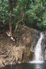 Uomo senza maglietta appeso sull'albero sopra stagno giungla — Foto stock