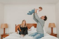Family playing with baby on bed in hotel — Stock Photo