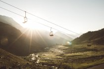 Picturesque view to ropeway moving over green mountains in sunset lights. — Stock Photo