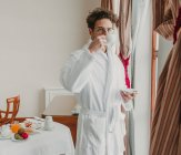 Handsome man standing in bathrobe and drinking from ceramic cup in hotel room. — стокове фото