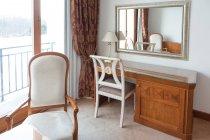 Деревянный стол со стулом и зеркалом в номере отеля . — стоковое фото