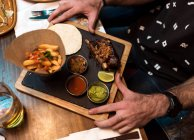 From above crop hands holding plate of food on cafe table. — Stock Photo