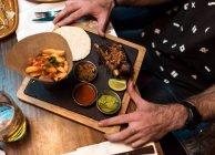 Par dessus des mains de récolte sur assiette de nourriture sur la table de café. — Photo de stock