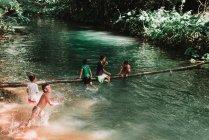 LAOS, LUANG PRABANG: Children swimming in lake and having fun on trunk bridge — Stock Photo
